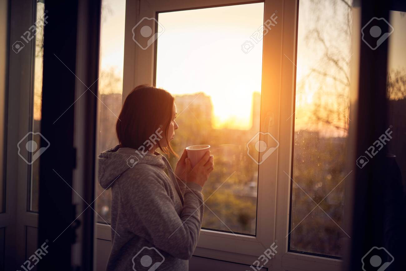 Woman near window at sunset in isolation at home for virus outbreak. Stay home concept. - 144235183