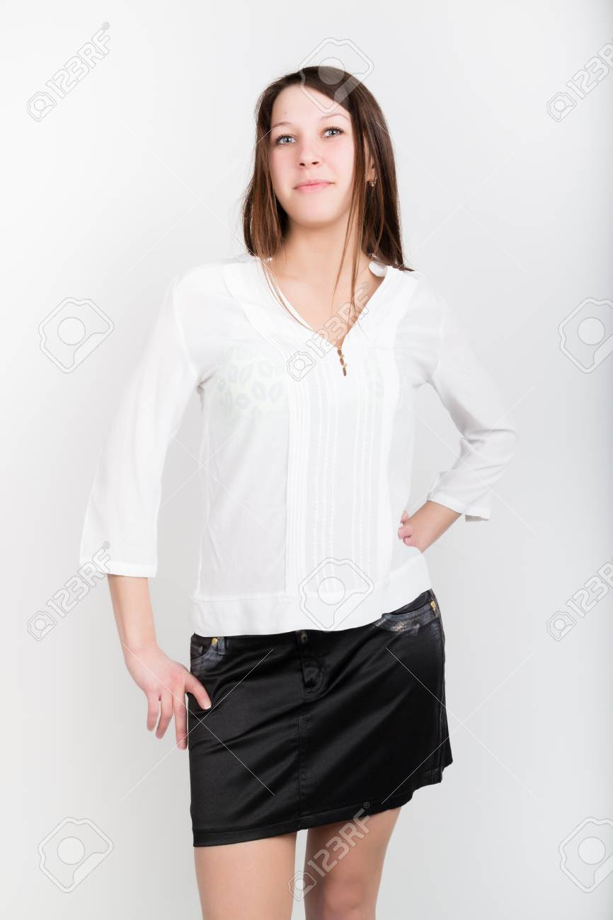 Beautiful slim girl in a short black skirt and white blouse,..