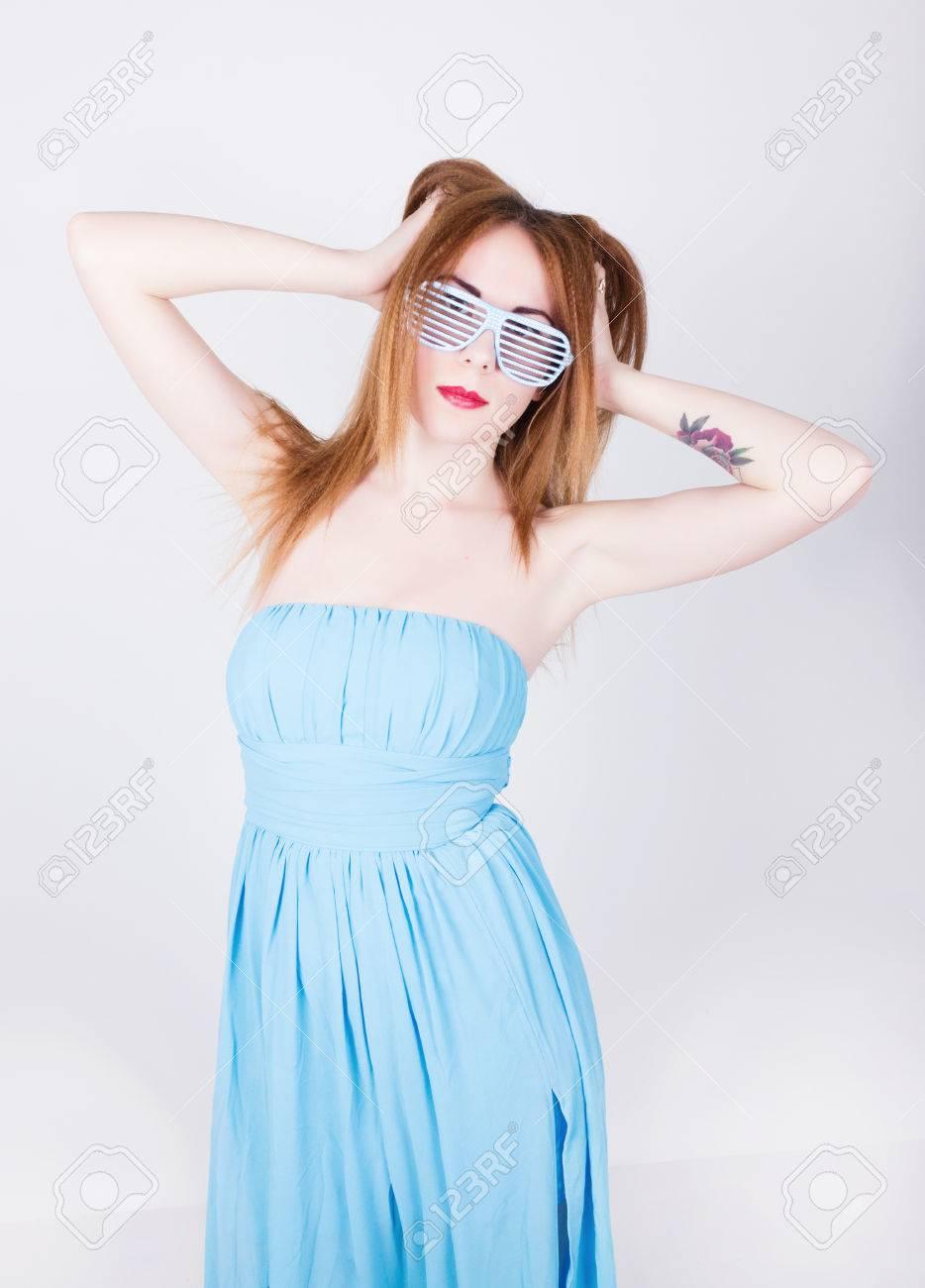 47ccd22f6 Foto de archivo - Niña en un vestido azul y gafas de sol en el estilo de la  música disco
