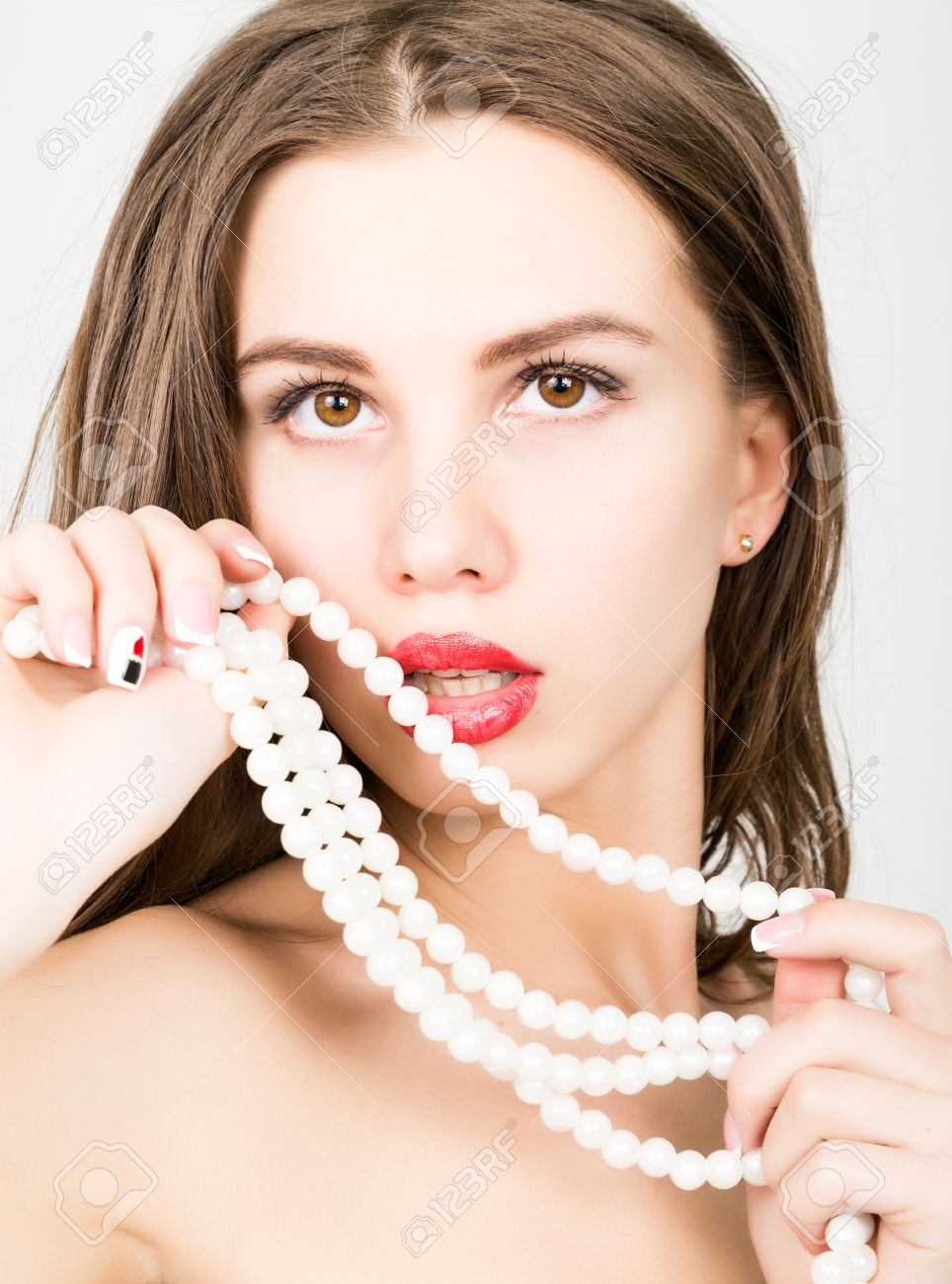 Stock Photo  Closeup Portrait Of A Beautiful Girl With Red Lips, Holding  A Pearl Necklace Mouth Open, Pearls Touches Her Lips