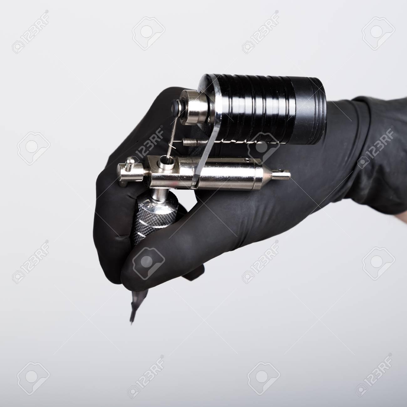 2f950804b42bb Banque d'images - Gros plan des mains dans des gants noirs tatoueur avec  machine à tatouer.