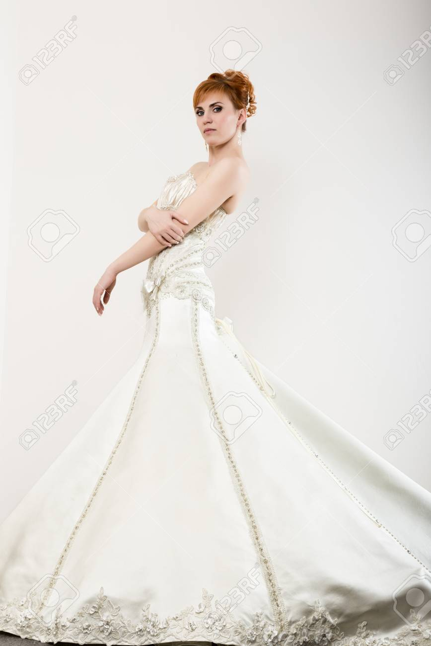Beautiful young redhead bride wearing white wedding dress with beautiful young redhead bride wearing white wedding dress with professional make up and hairstyle junglespirit Image collections