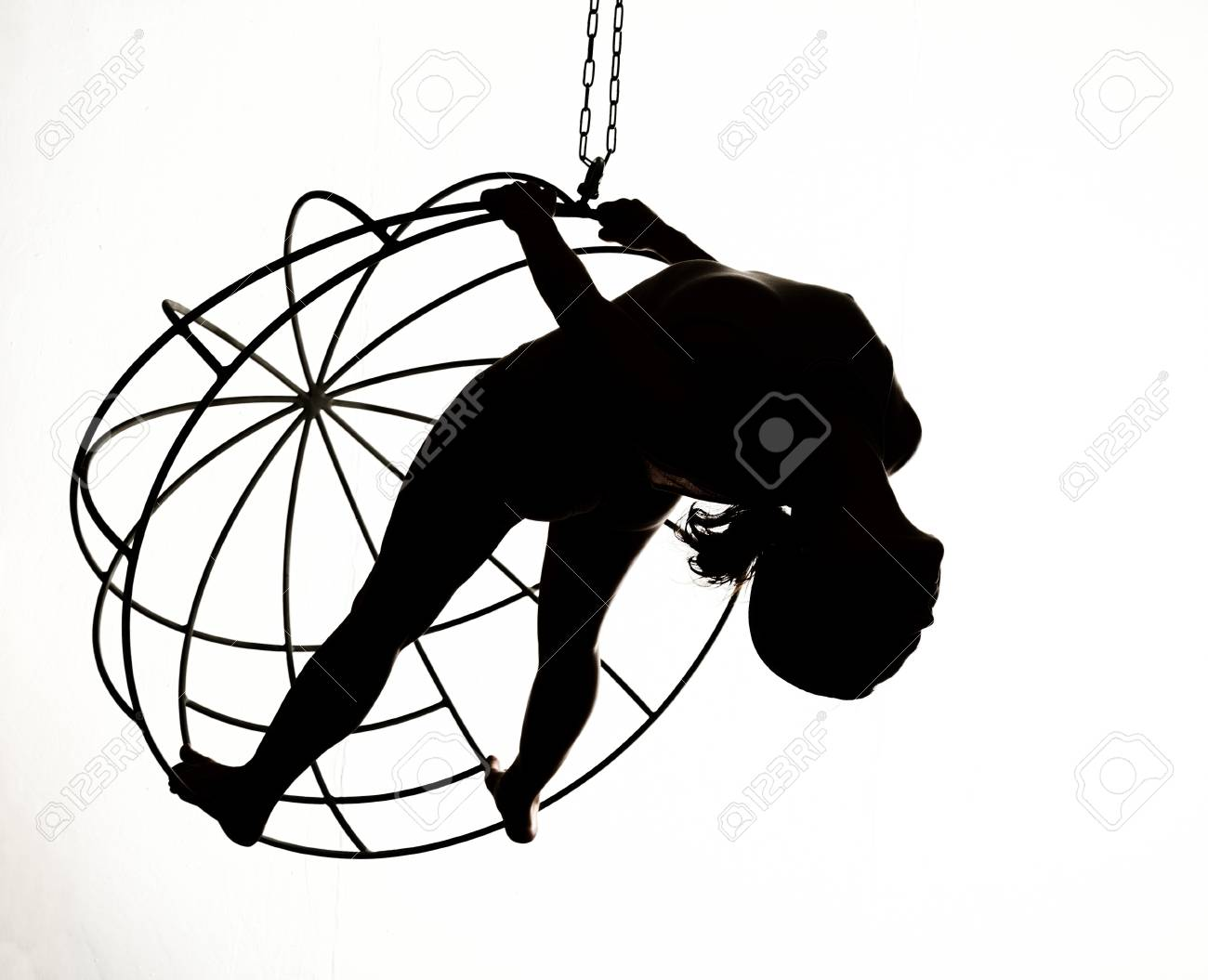 Silhouette of a sexy woman on a metal swing, black and white Stock Photo -