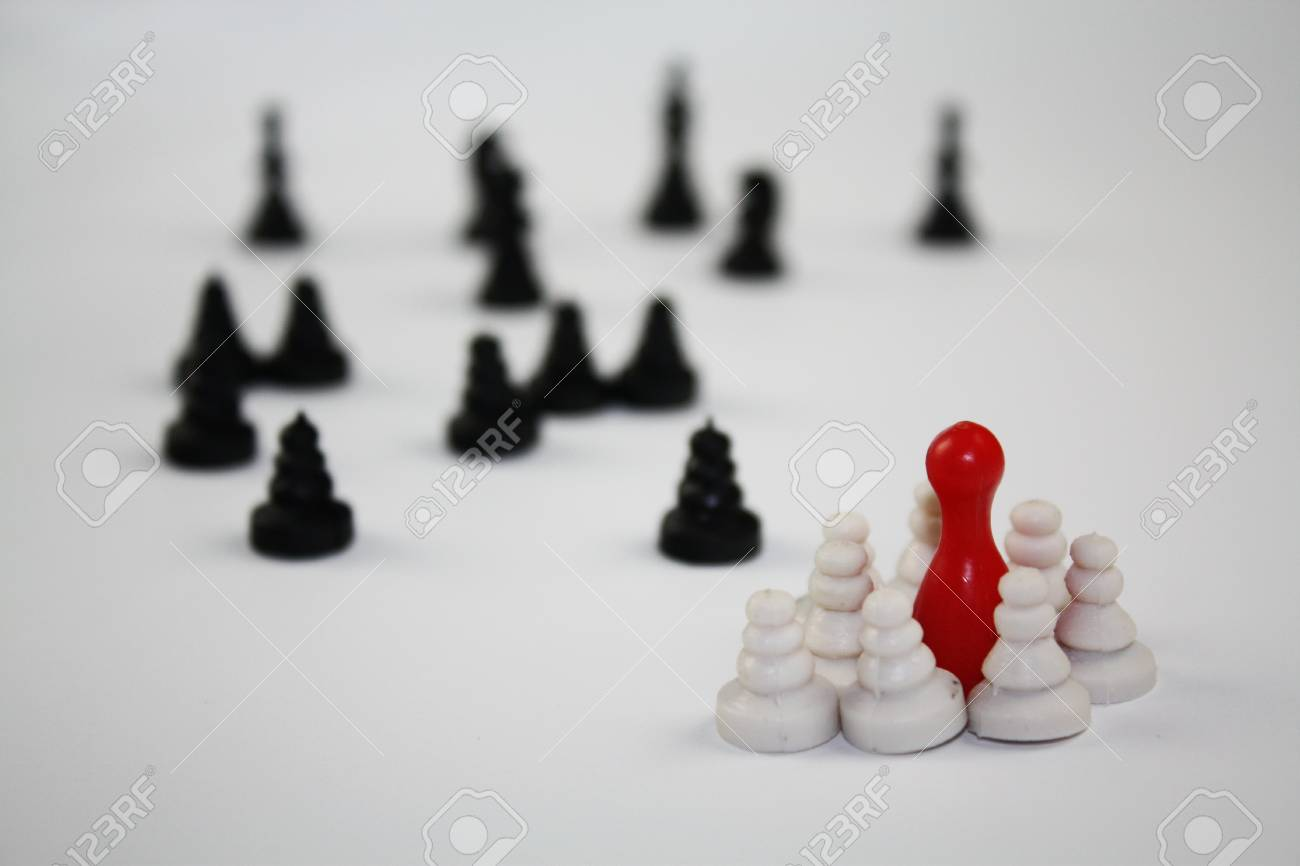 Two groups of chess pieces and one red ludo figurine middle the white group. - 92914502