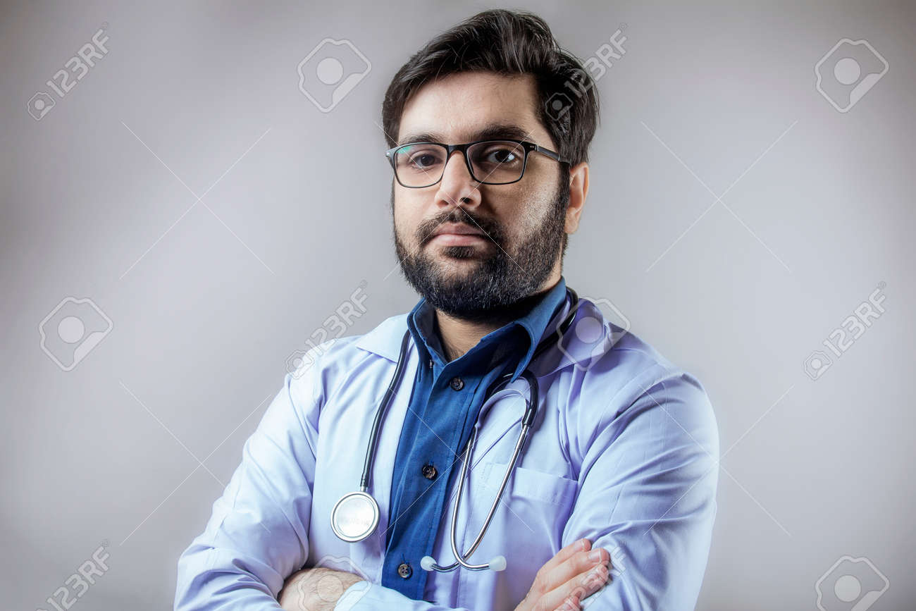 A doctor wearing stethoscope and medical coat looking forward - 167104183