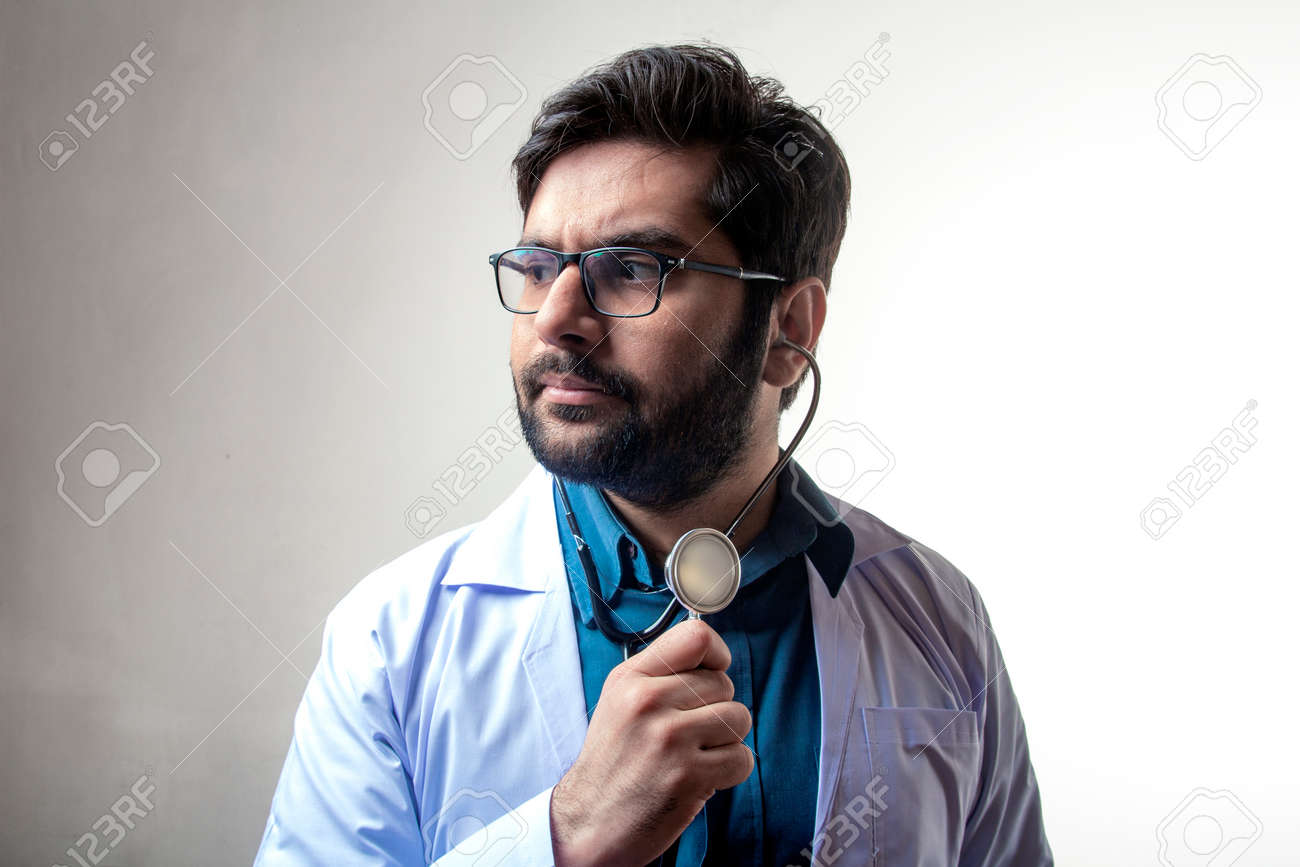 A doctor wearing stethoscope and medical coat looking forward - 167104185