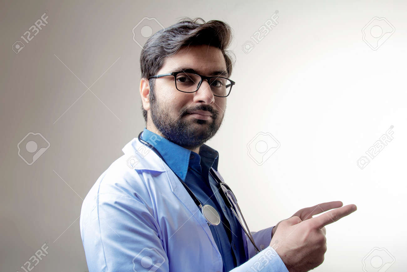 A doctor wearing stethoscope and medical coat looking forward - 167104188