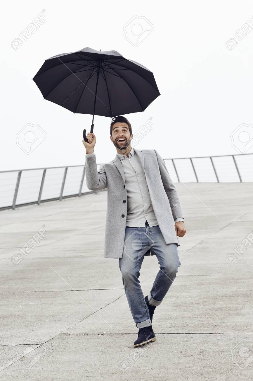 excited guy with umbrella looking up stock photo picture and