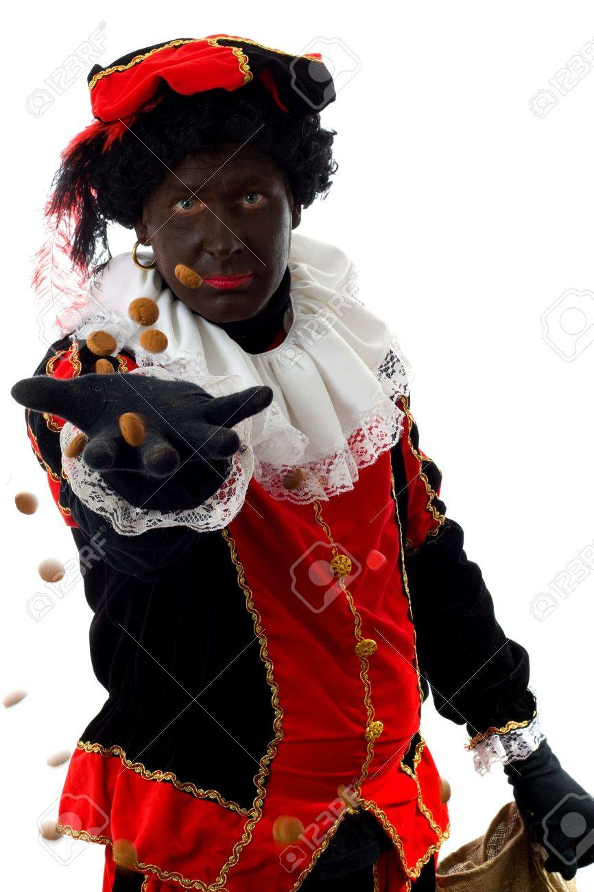 Zwarte piet ( black pete) typical Dutch character part of a traditional event celebrating the birthday of  Sinterklaas in december over white background throwing pepernoten ( ginger nuts) Stock Photo - 6037991