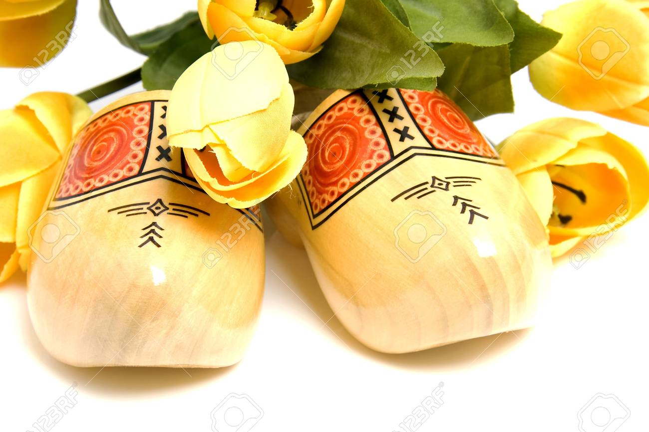 Typical Dutch wooden shoes with silk yellow tulips over white background Stock Photo - 6756761