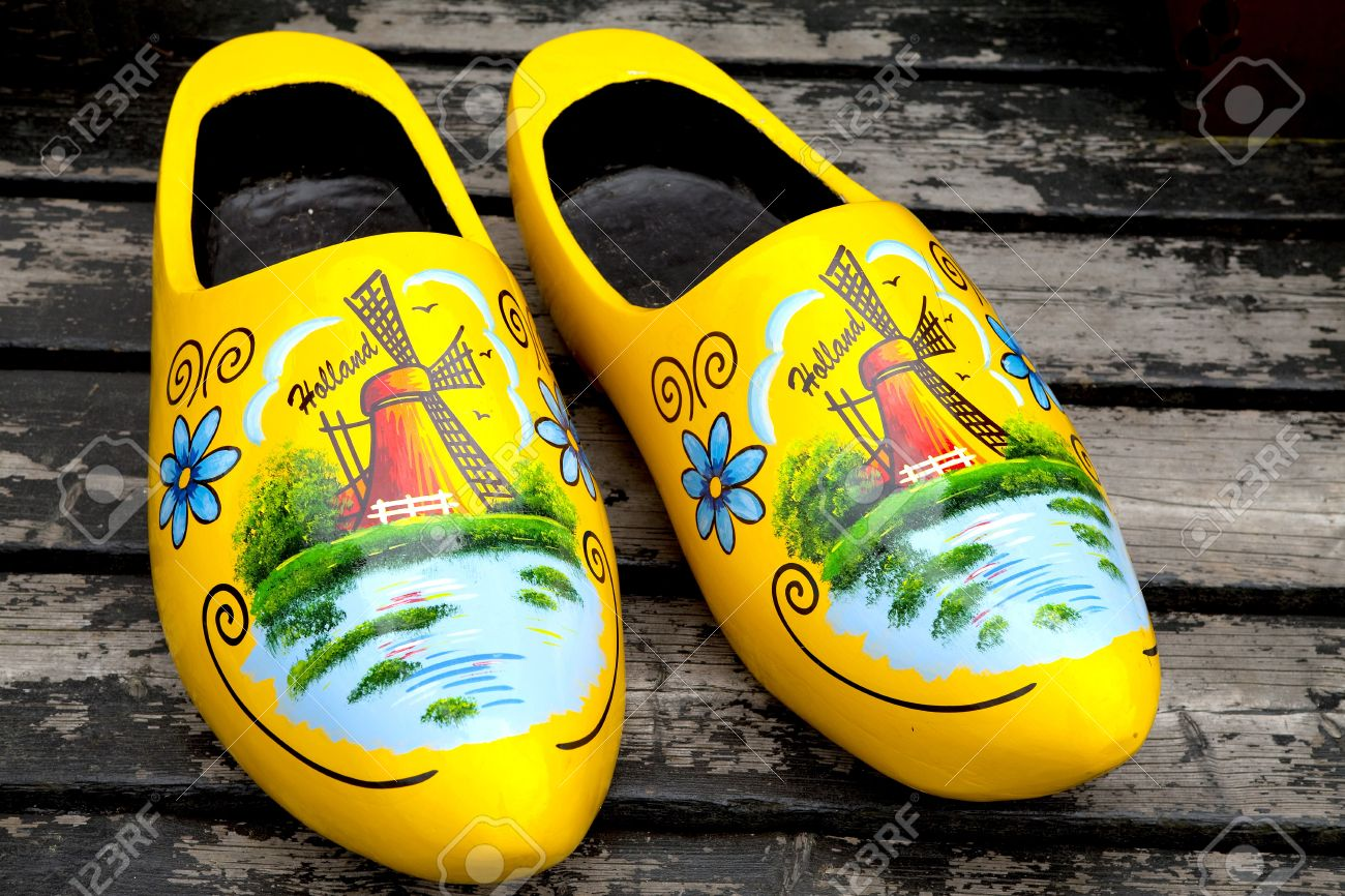 painted typical dutch yellow wooden shoes in closeup stock photo