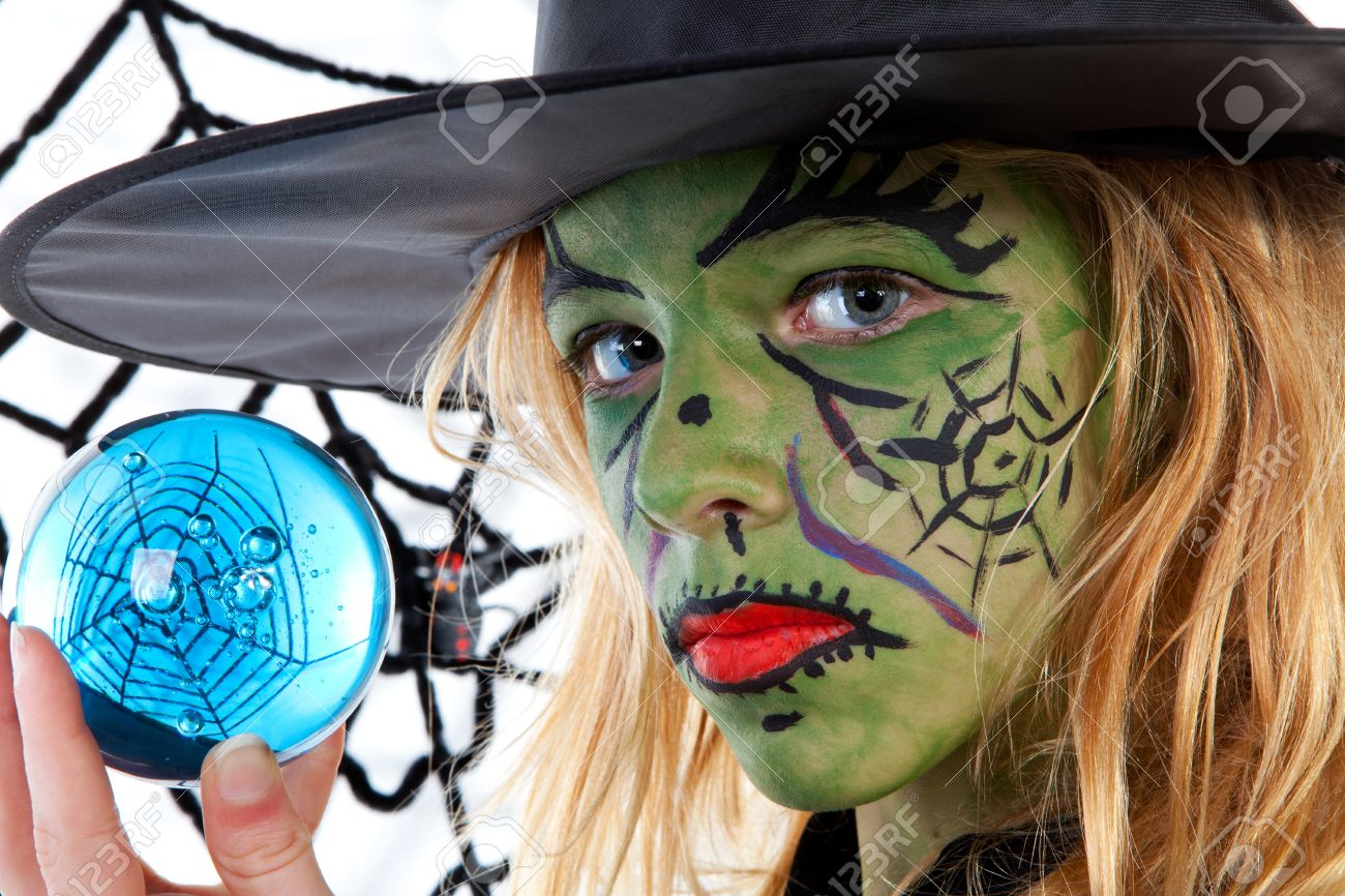 Portrait of green Halloween witch girl holding big blue marble in closeup Stock Photo - 10644865