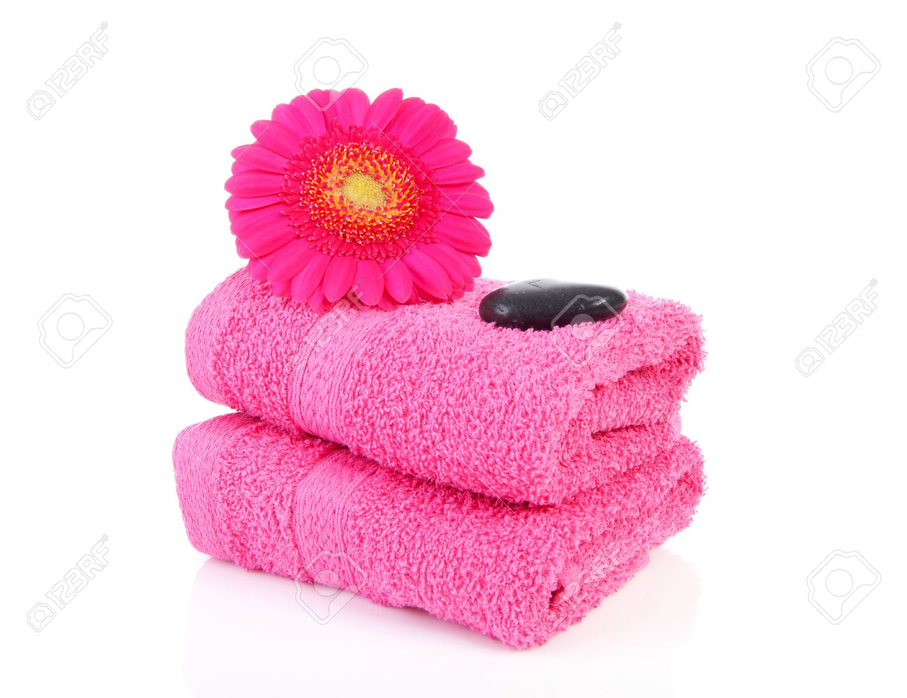 Pink and white bathroom accessories - Pink Bathroom Accessories With Towel Stones And Gerber Flower Over White Background Stock Photo