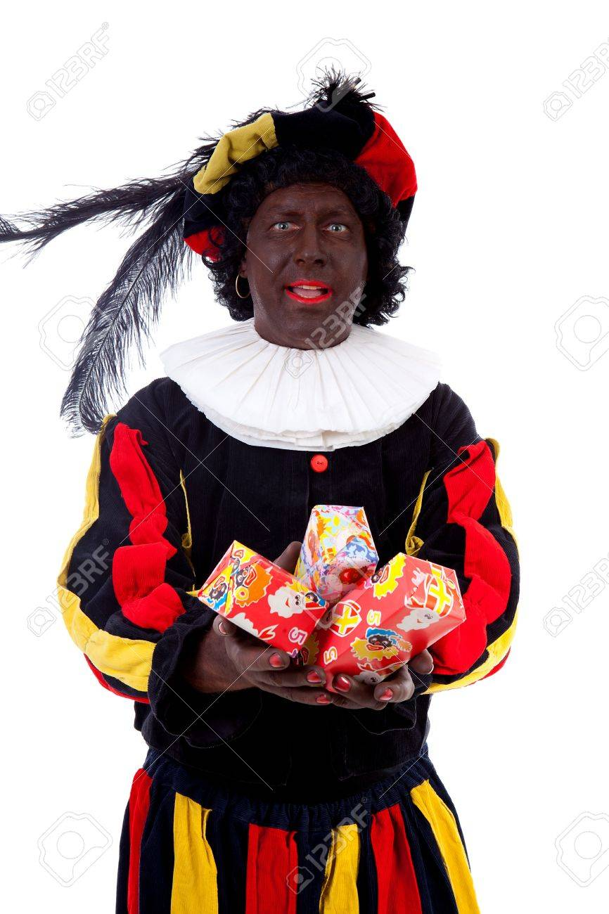 Zwarte piet ( black pete) typical Dutch character part of a traditional event celebrating the birthday of Sinterklaas in december over white background with presents Stock Photo - 16591415