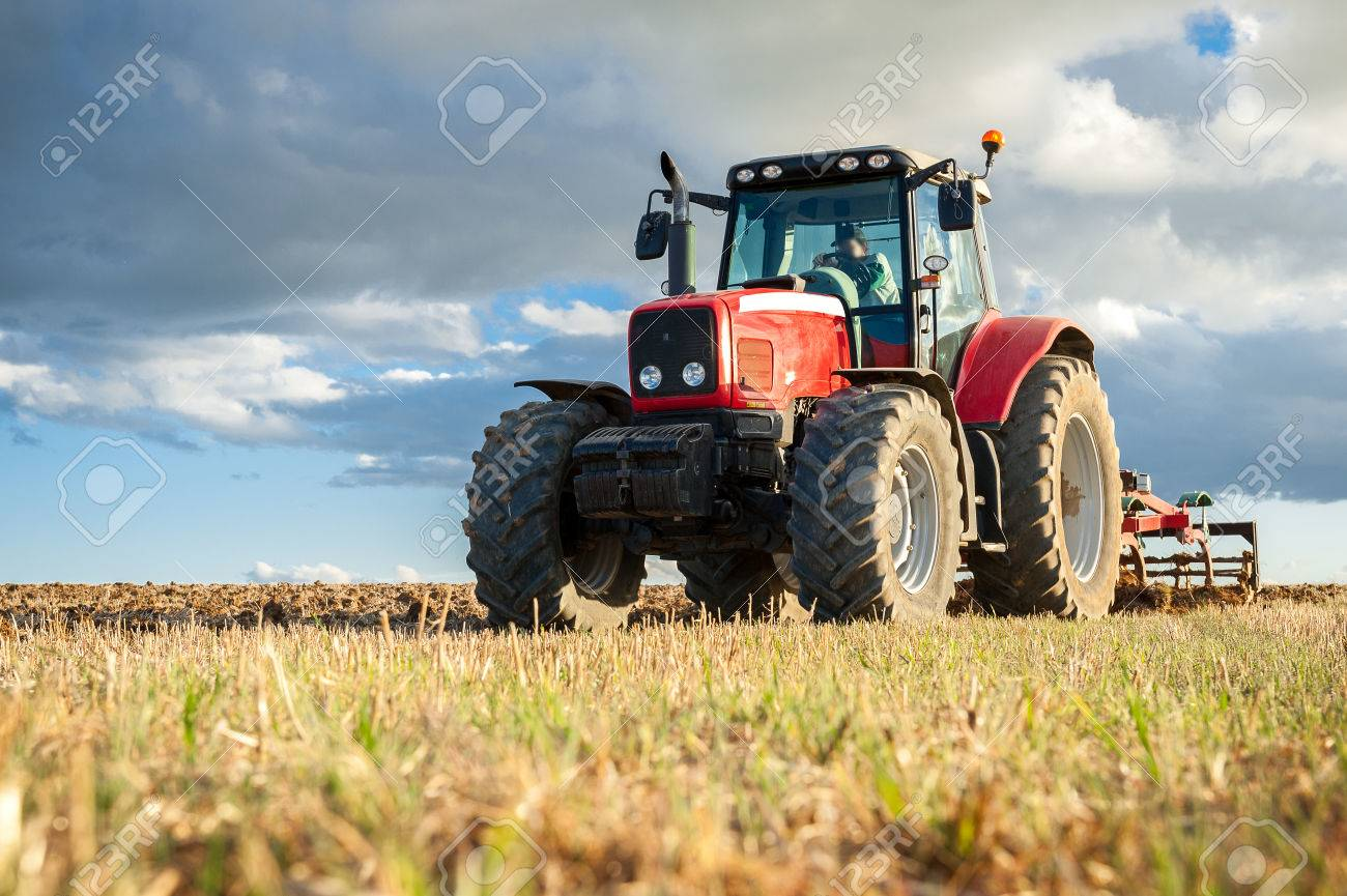 agricultural machinery in the foreground carrying out work in the field - 82343940
