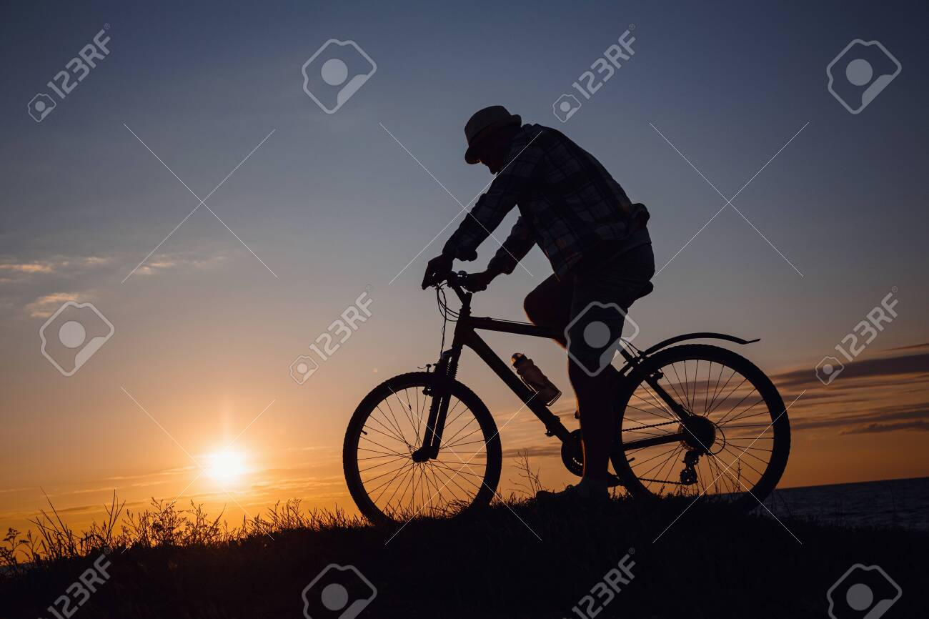 silhouette of a hipster man on a bicycle on sunset background. Idea and concept of physical activity and healthy lifestyle - 144724322