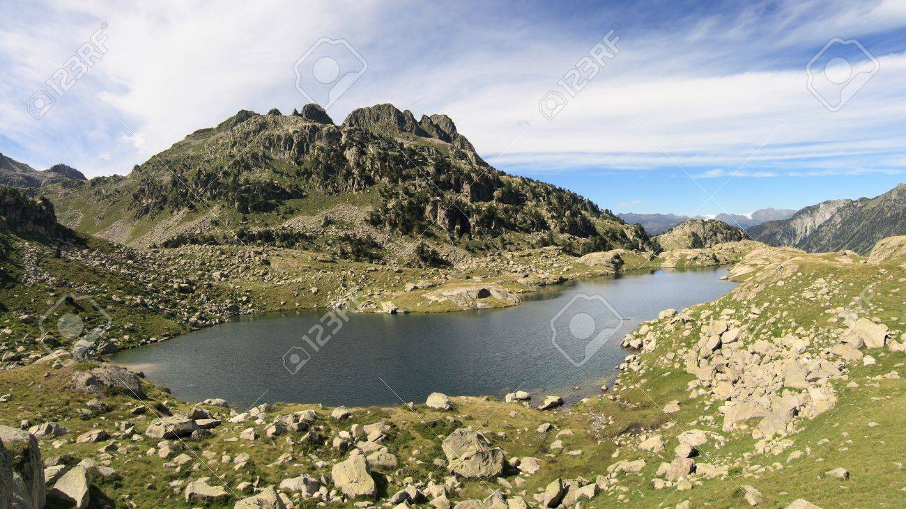 Lake Estanh Mort with mountain and cirrus clouds, in the Colomers lakes area in the catalan Pyrenees Stock Photo - 20102821