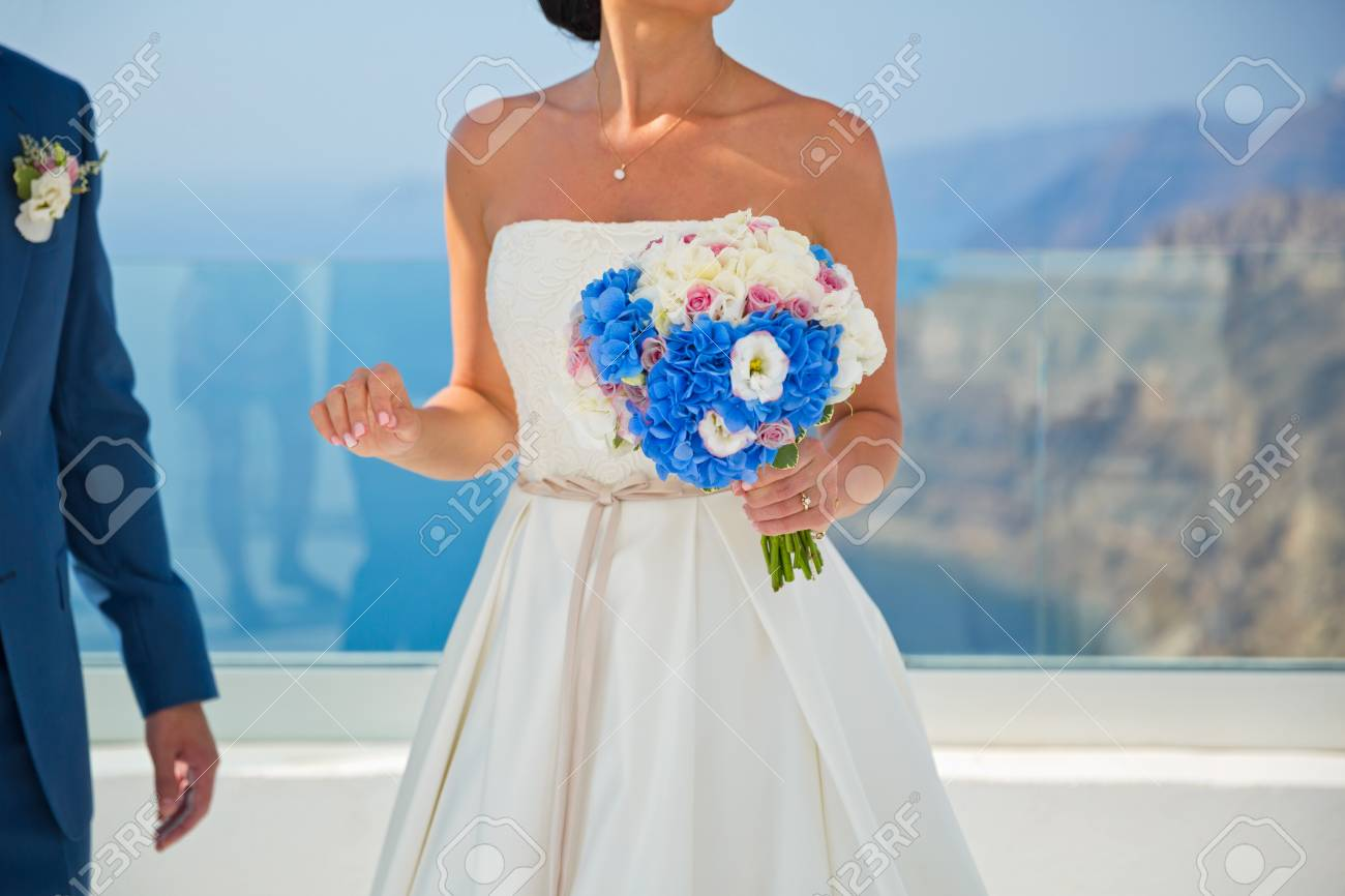 Seaside wedding and bride in a white dress with a bouquet of stock seaside wedding and bride in a white dress with a bouquet of blue flowers stock photo izmirmasajfo