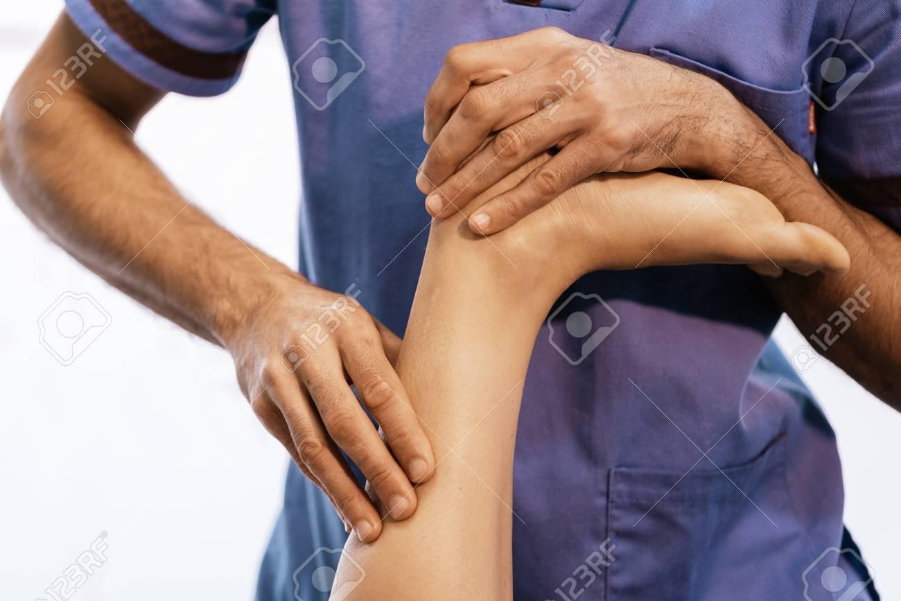Physiotherapist giving knee therapy to a woman in clinic. Physical treatment concept - 121377275