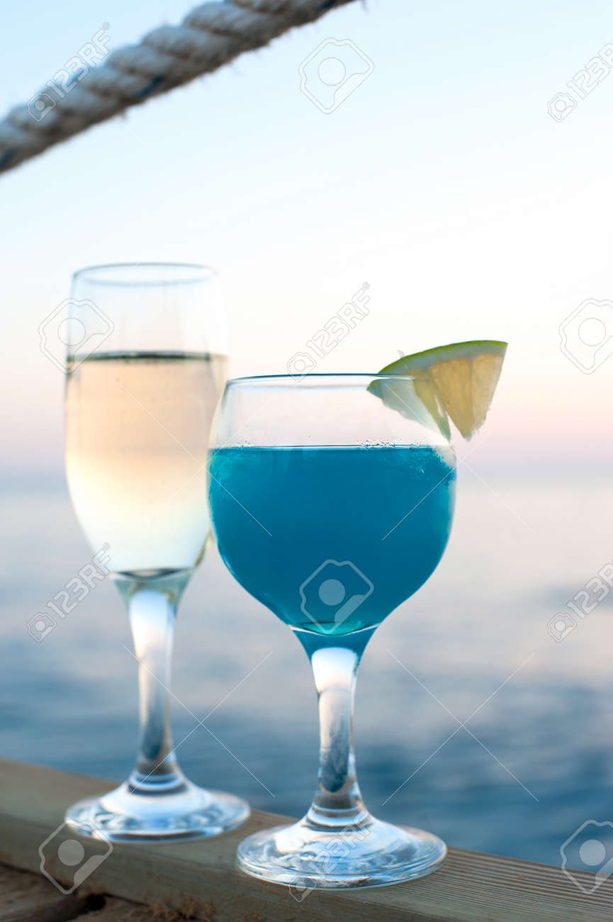 Two glasses with white wine and fresh blue cocktail drink standing on wooden pier at sunset. Vibrant summertime outdoors vertical image with blue ocean background. - 129921609