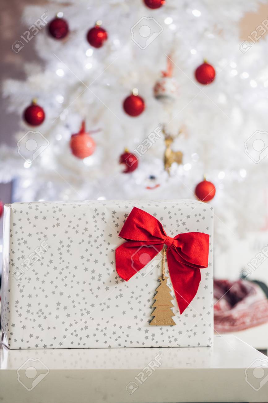 Gift With Red Bow And Card, In Front Of White Christmas Tree ...