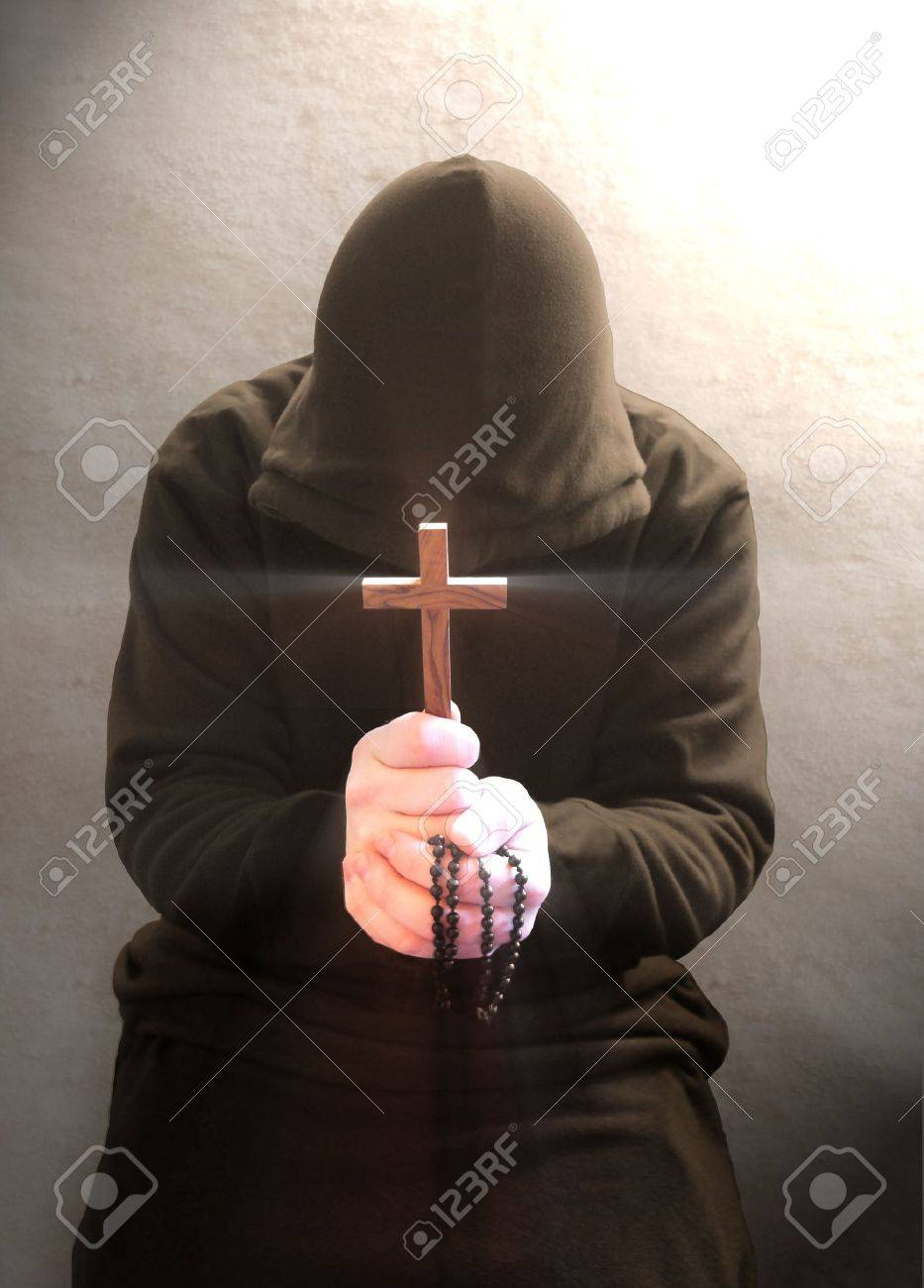 A monk praying with a rosary and crucifix in his hand. Stock Photo - 2668680