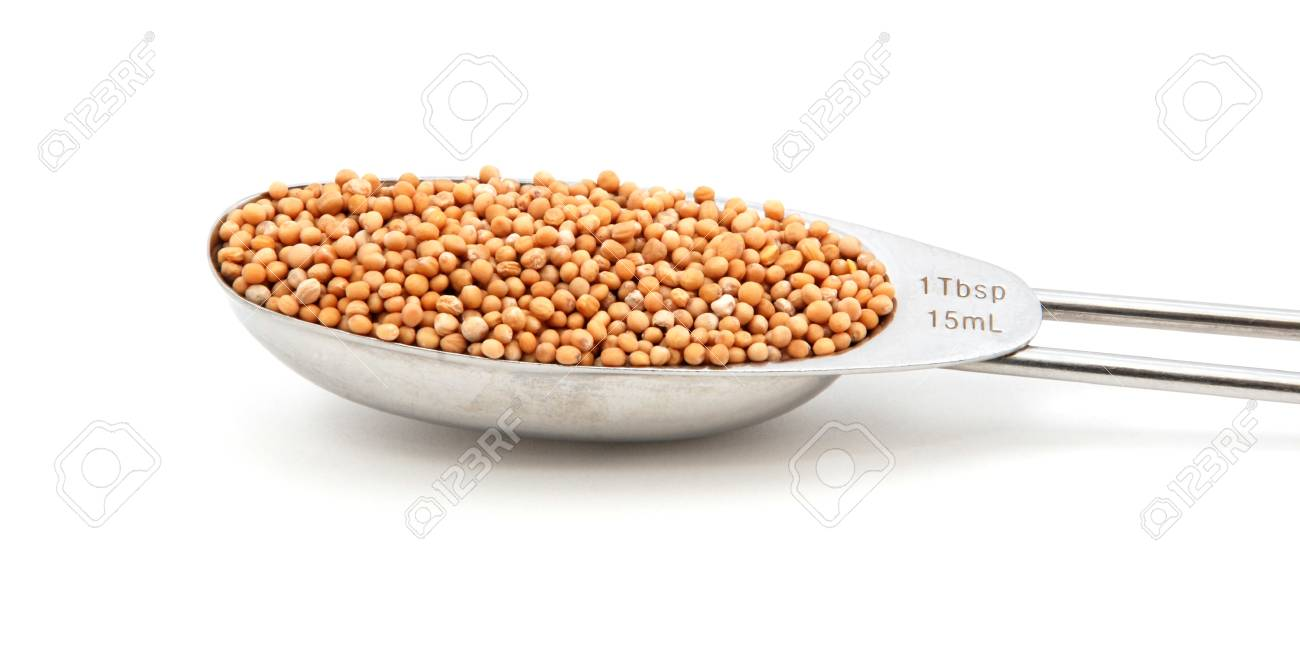 Mustard seeds measured in a metal tablespoon, isolated on a white background Stock Photo - 17599697