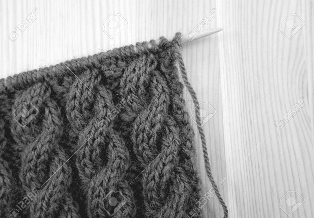 Coiled Rope Cable Knitting Stitch On The Needle On A Wooden