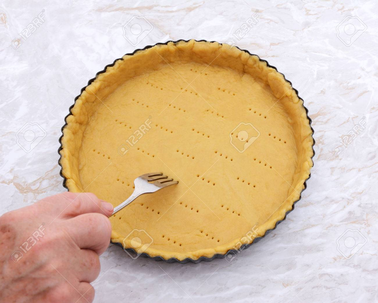 Woman Finishes Pricking Holes In A Shortcrust Pastry Pie Crust