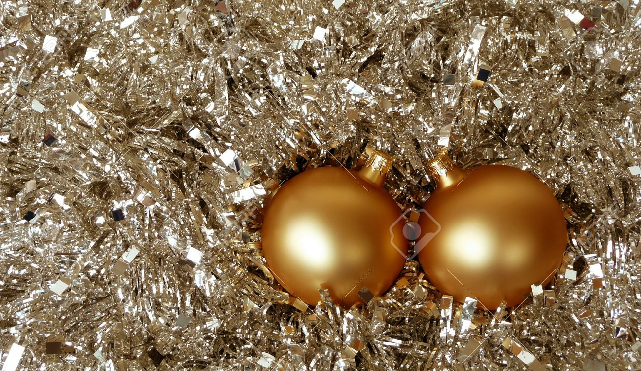 Pair Of Gold Christmas Tree Balls In Background Silver Xmas Tinsel Stock Photo