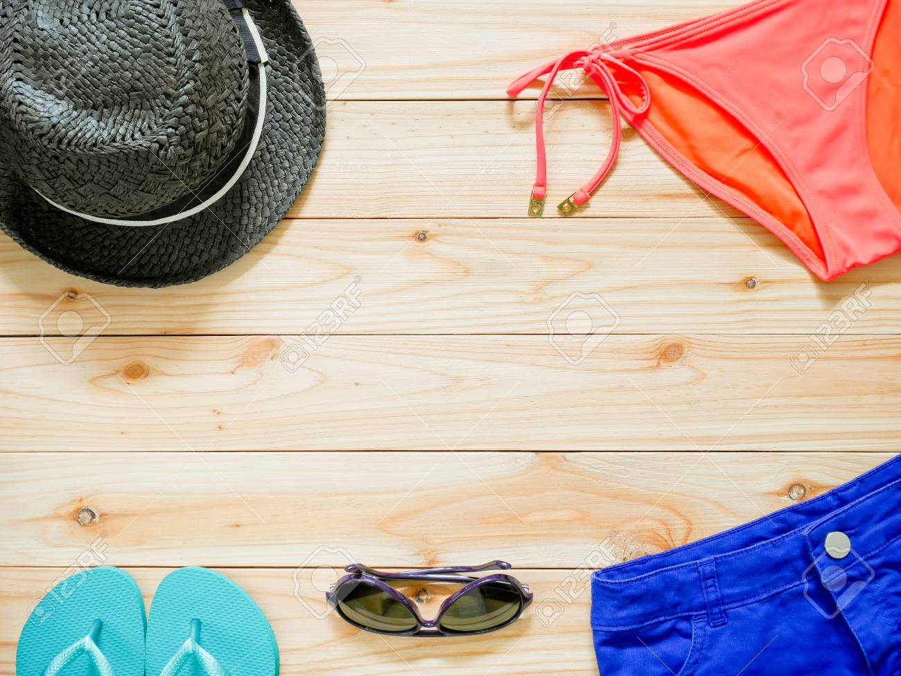 4b82afaf9a Stock Photo - Women's beachwear and accessories on wooden background. Beach  clothing concept.