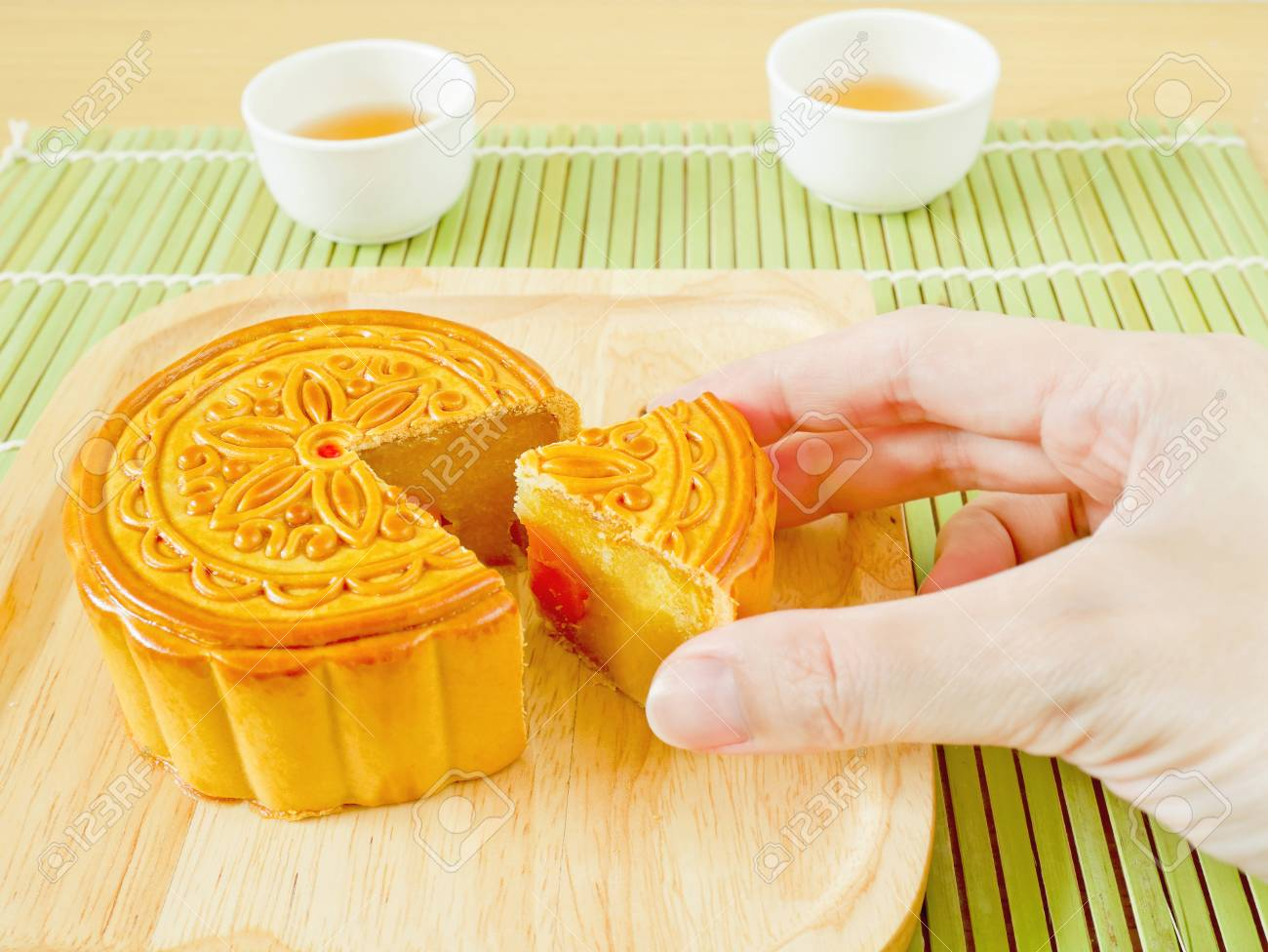 Hand picking durian mooncake with salted egg yolk on Mid-Autumn