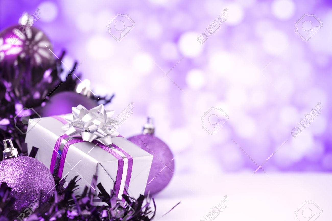Christmas Purple.Purple And Silver Christmas Baubles And A Gift In Front Of Defocused