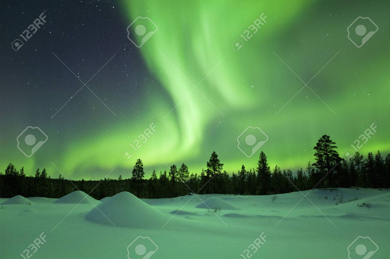 Spectacular aurora borealis northern lights over a snowy winter landscape in Finnish Lapland. - 43325798