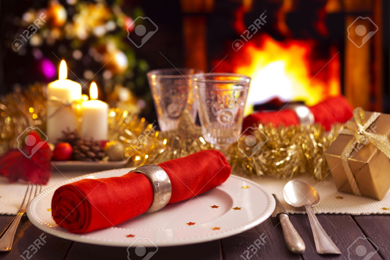 A Romantic Christmas Dinner Table Setting With Candles And Christmas