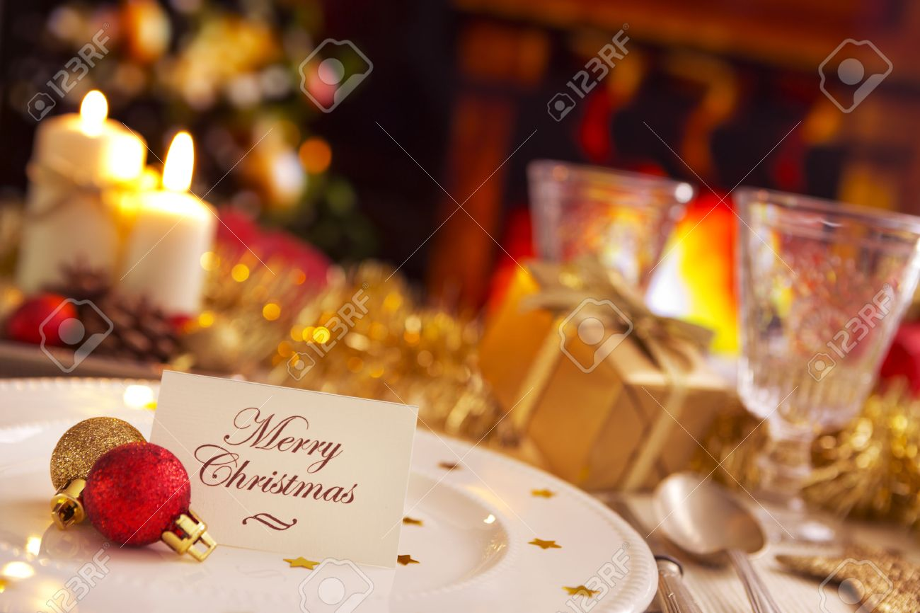 a romantic christmas dinner table setting with candles and christmas decorations on the plate a