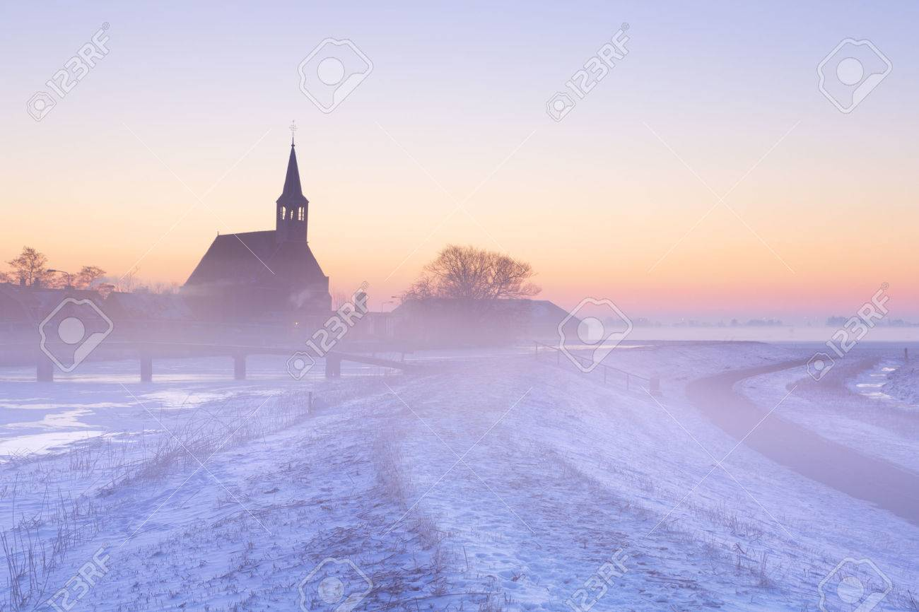 A church in a frozen winter landscape in The Netherlands. Photographed at sunrise on a beautiful foggy morning. - 50981513