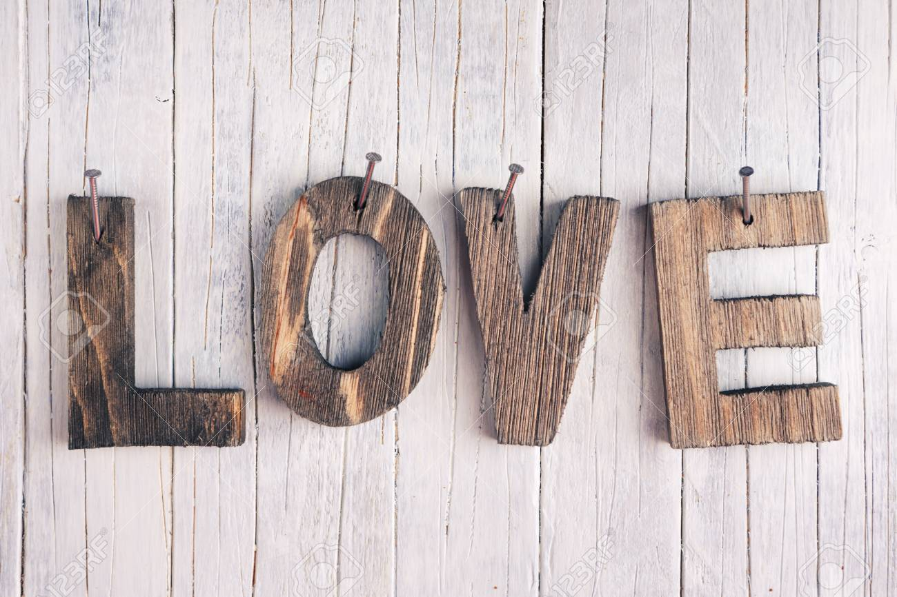 stock photo the word love in wooden letters nailed on a rustic wooden background