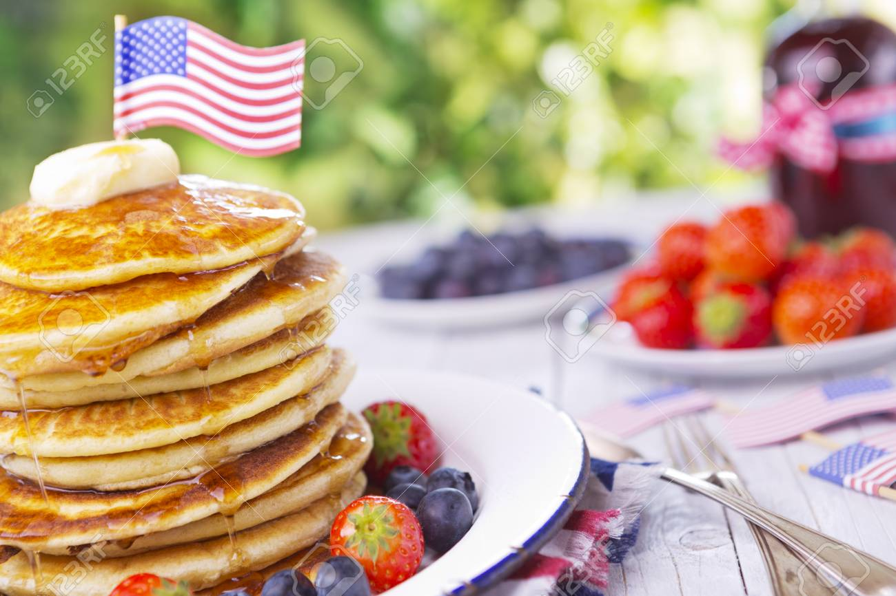 A stack of homemade pancakes with fresh fruit, butter and syrup. - 53956553