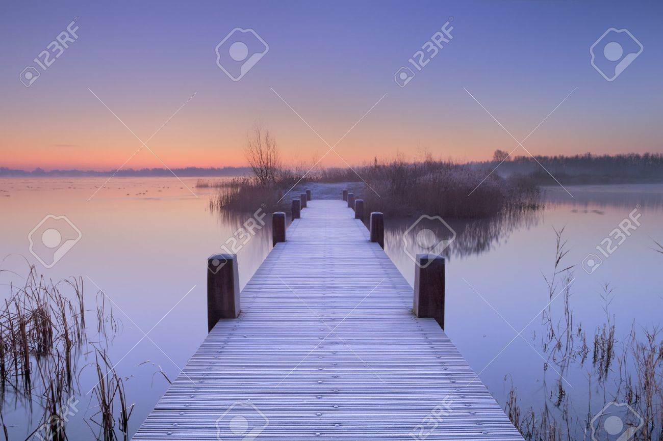 A quiet lake in The Netherlands with a boardwalk on an early morning. - 65720799