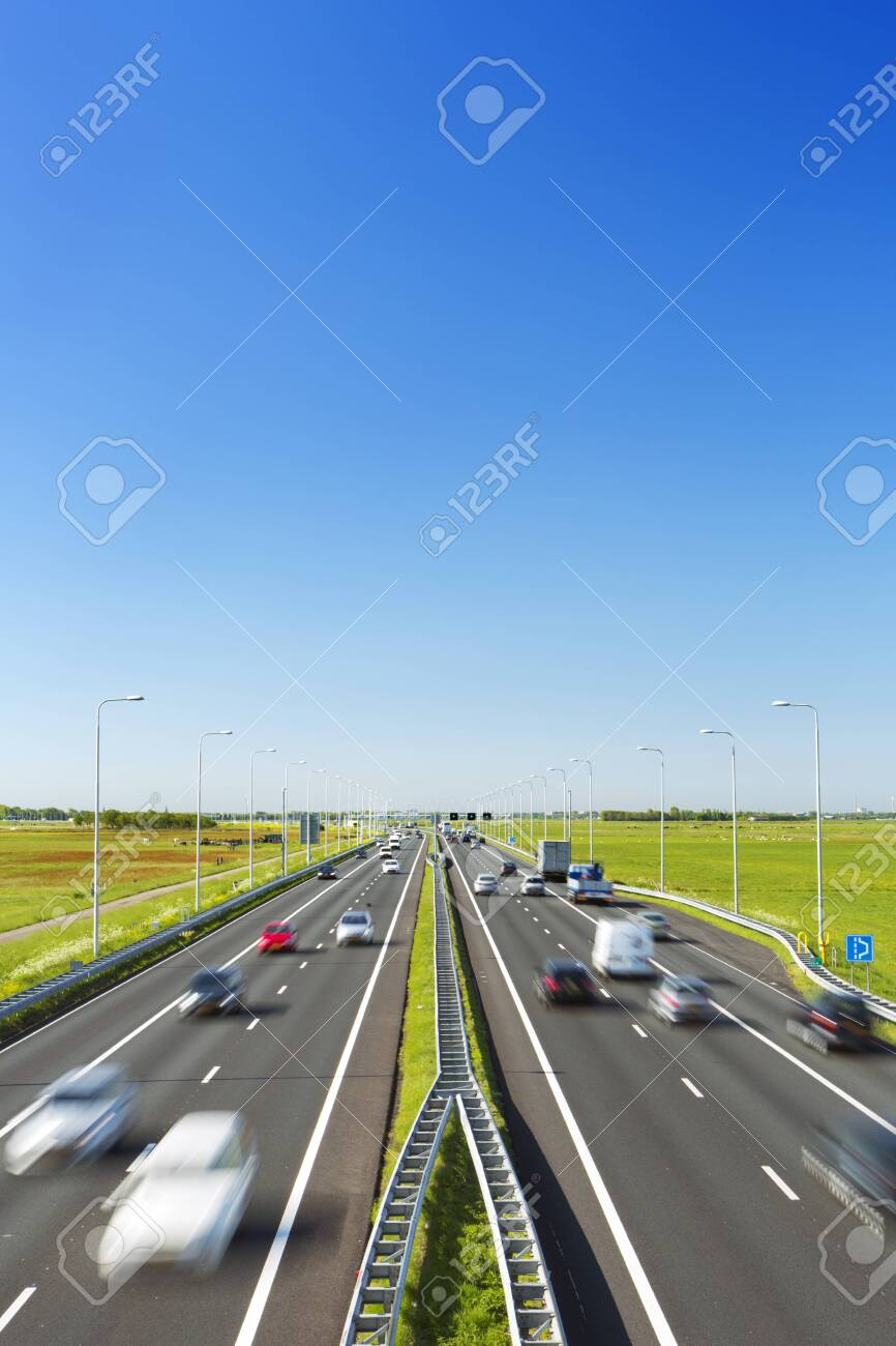A highway with traffic through grassy fields on a bright and sunny day in The Netherlands. - 135125194