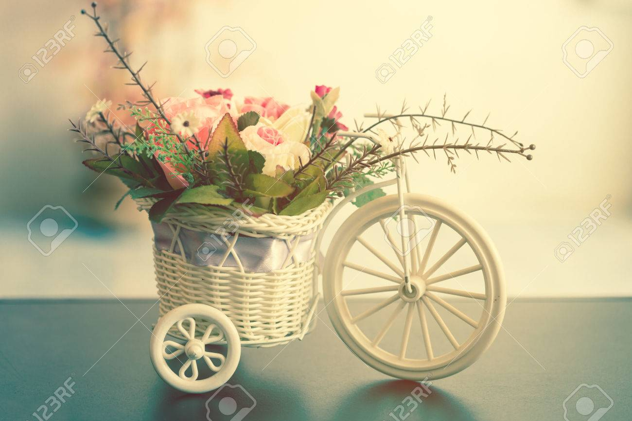 Artificial flowers in a white bicycle basket on black table artificial flowers in a white bicycle basket on black table vintage style stock photo mightylinksfo