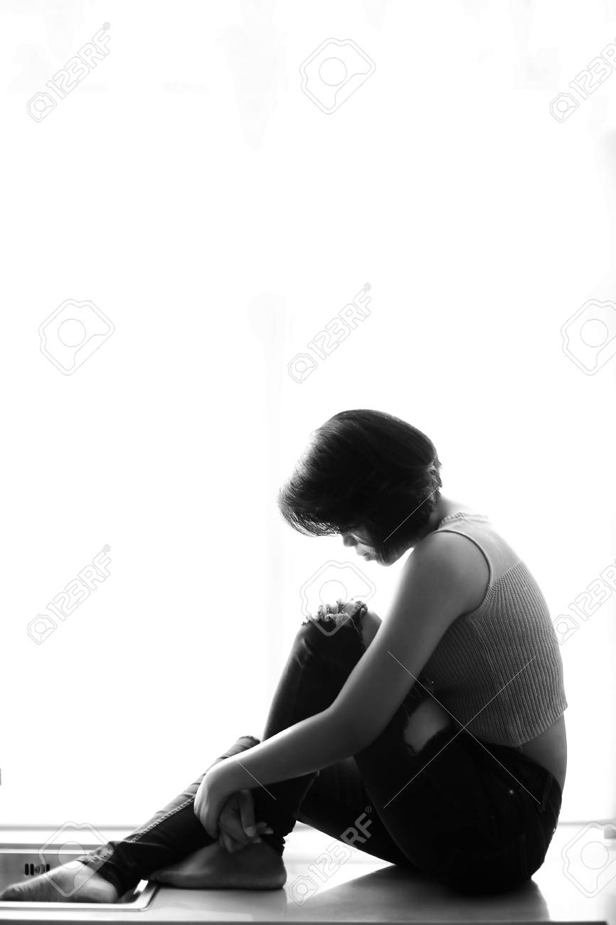 Sad girl sad woman silhouette sitting alone on white background stock photo 102981149
