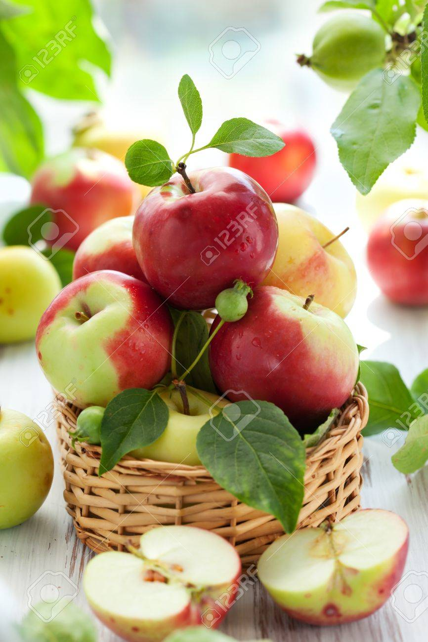 Red,green and yellow apples with leaves in the basket Stock Photo - 9967204