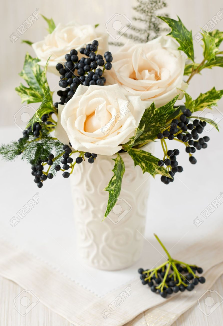 Christmas arrangement of roses,winter berries and holly Stock Photo - 10563457