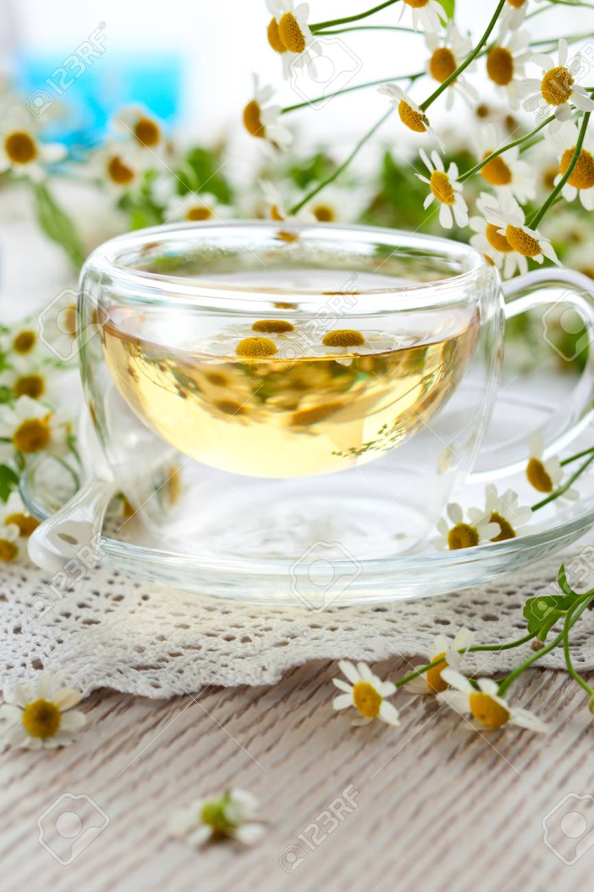 Chamomile tea in glass cup with flowers Stock Photo - 13509236