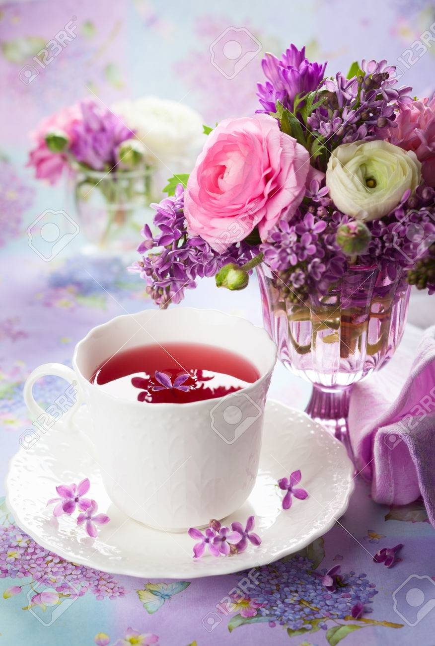 Beautiful spring flowers in vase and cup of tea Stock Photo - 25946554