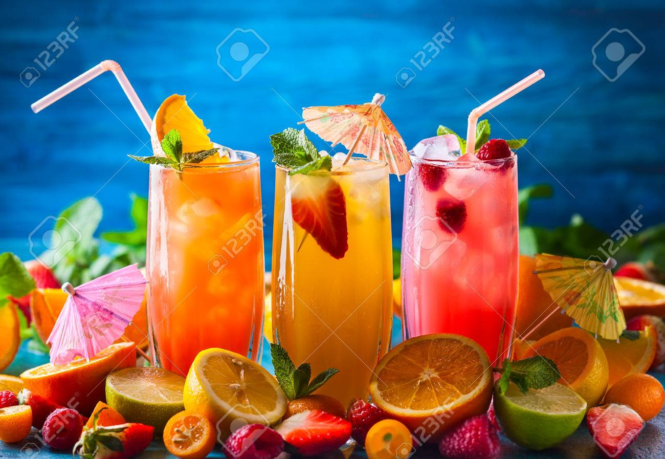 Different types of summer drinks in glasses, cubes of ice and slice of fruits on blue table. Healthy vitamin fruit and berry drinks. - 76667018