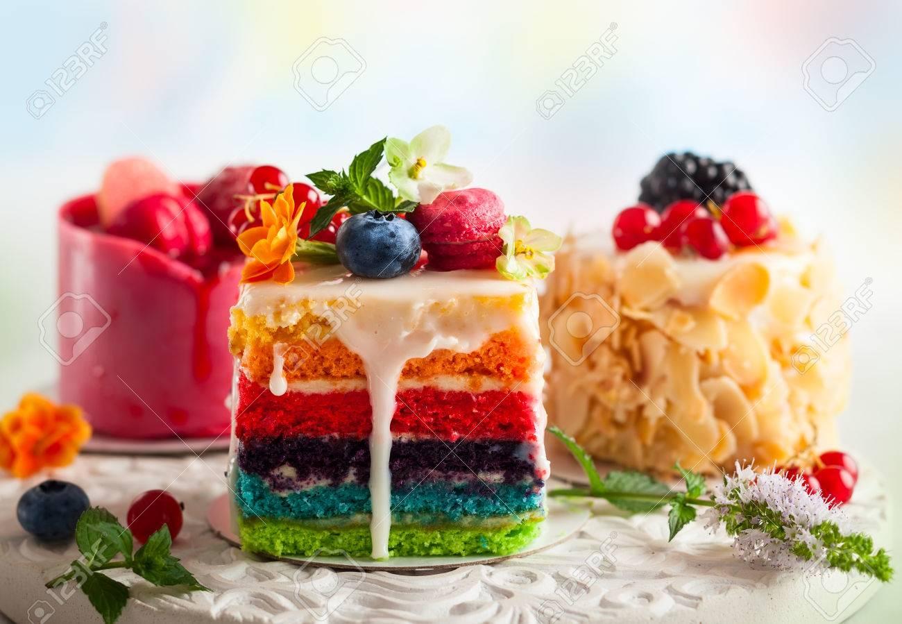 Various slices of cakes on a white tray rainbow cake, raspberry..