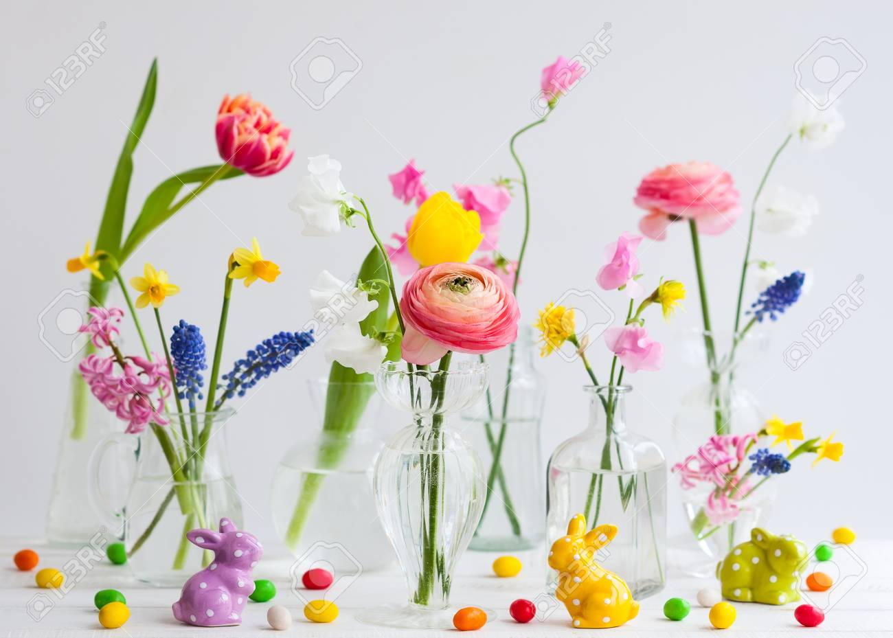 Beautiful flowers bouquets in glass vases on festive Easter table. Colored Easter eggs in egg cups - 93388904